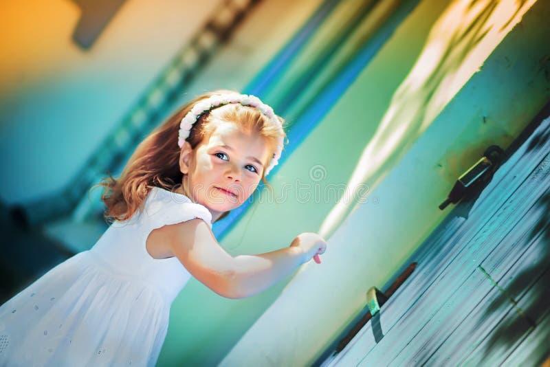 Lilla flickan i en blå klänning knackar på fönstret fotografering för bildbyråer