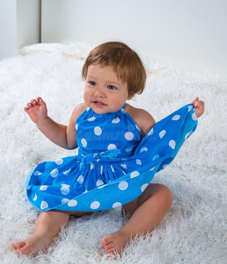 Lilla flickan i en blå klänning sitter på sängen och rymmer kanten av hennes klänning arkivfoto