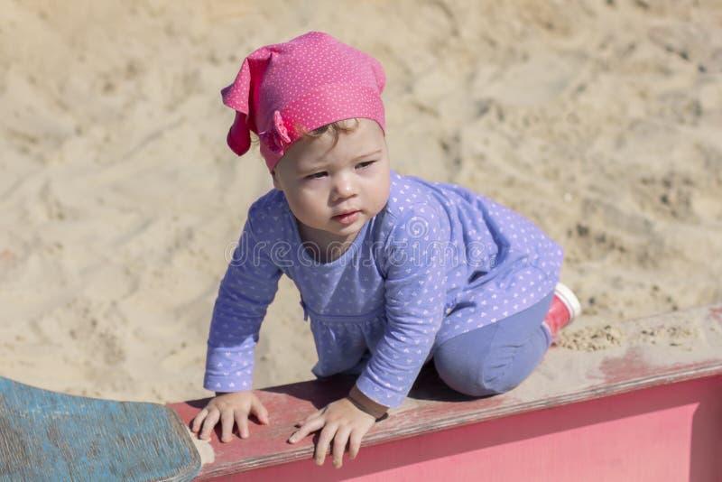 Lilla flickan i en blå klänning står på alla fours på kanten av sandlådan, sommar som den soliga dagen går arkivfoton
