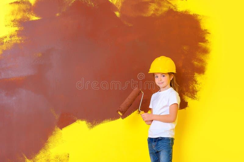 Lilla flickan i en konstruktionshjälm målar väggen med en rulle royaltyfri foto