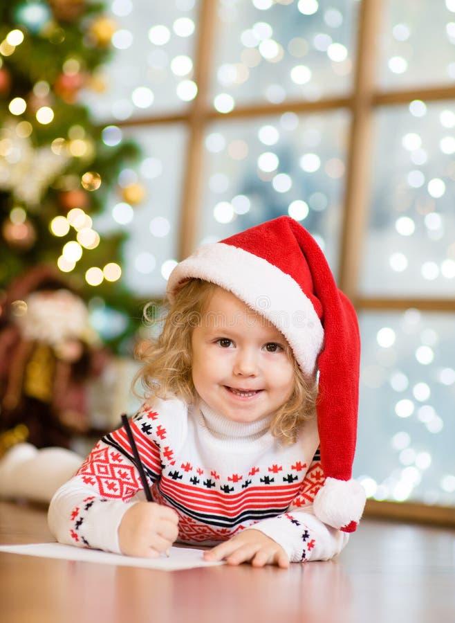 Lilla flickan i en röd julhatt skrivar brevet till Santa Claus fotografering för bildbyråer