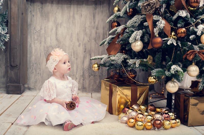 Lilla flickan i en smart klänning sitter nära en julgran arkivfoto