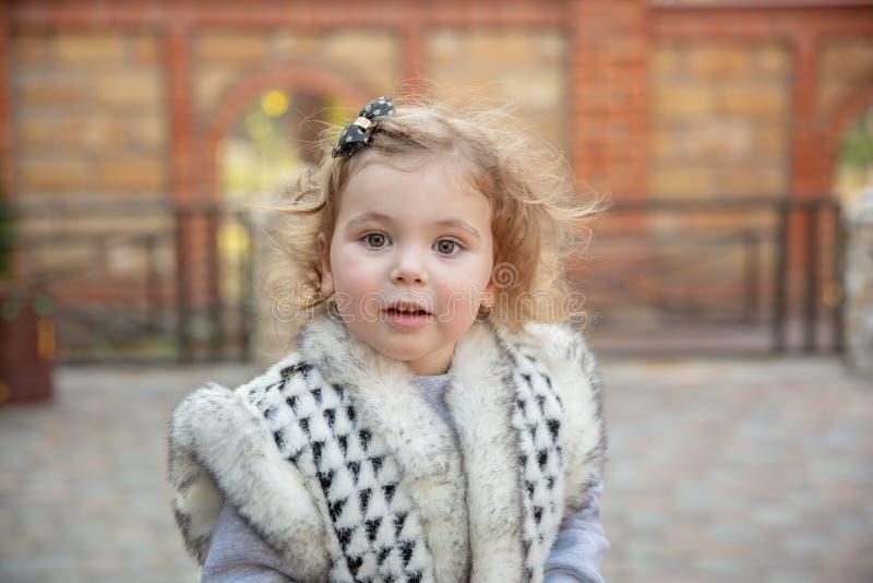 Lilla flickan i en stads- inställning ler på kameran arkivfoton
