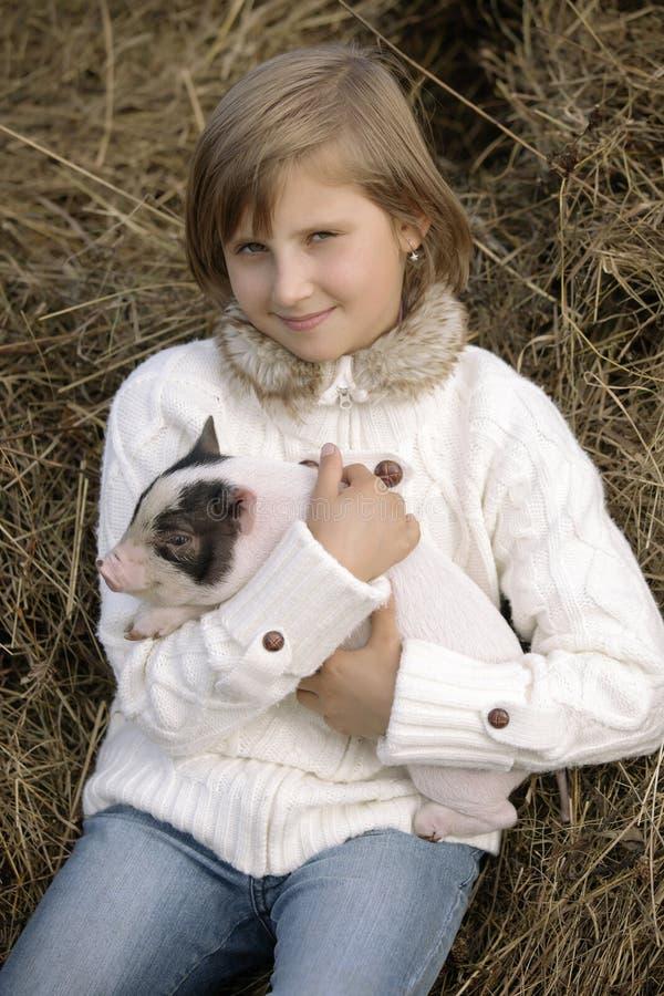 Lilla flickan i en vit blus sitter och rymmer en spädgris och ler Livsstilstående royaltyfria foton