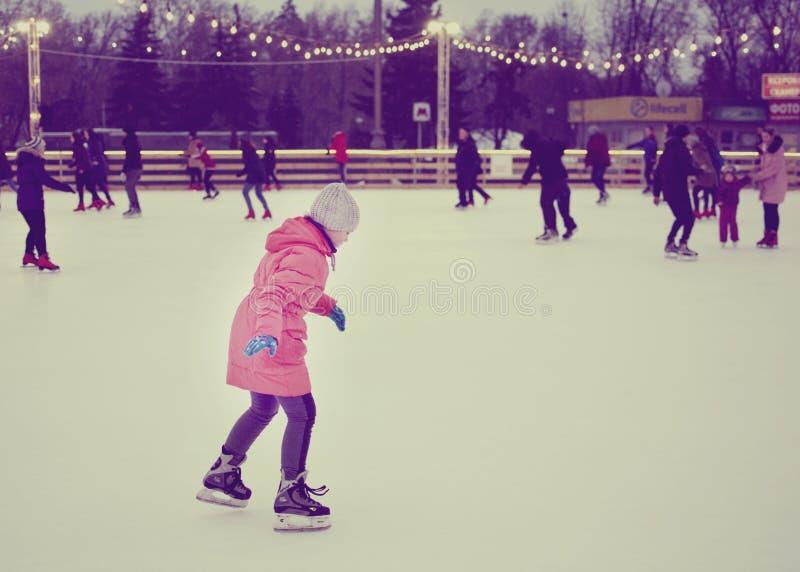 Lilla flickan i ett rosa omslag åker skridskor på en öppen åka skridskor isbana royaltyfria foton