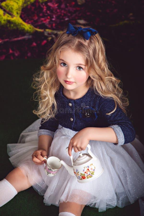 Lilla flickan i härlig klänning och blått bugar hällande te arkivfoto