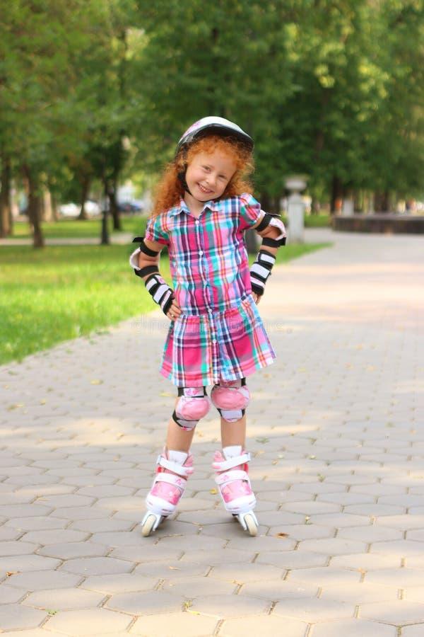 Lilla flickan i hjälmrullskridskor i grön sommar parkerar royaltyfri bild