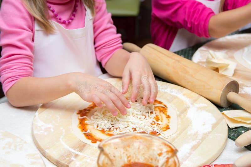 Lilla flickan i kockhatt lagar mat pizza royaltyfri fotografi