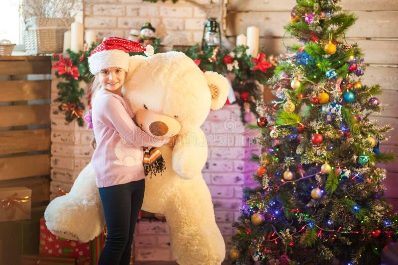 Lilla flickan i locket av Santa Claus väntar på det nya året med ett Big Bear i hans händer Julflicka med gåvor i en rus royaltyfri fotografi