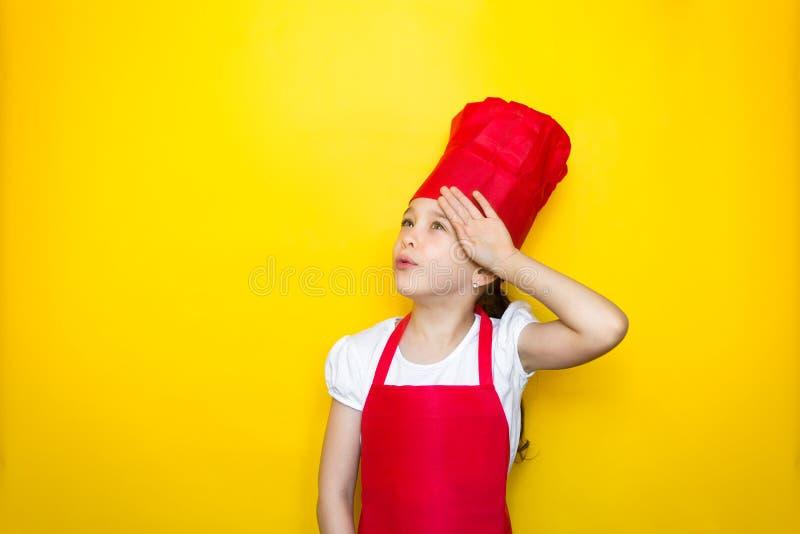 Lilla flickan i röd en kocks dräktflicka är trött av att laga mat, torkar hans handpanna på gul bakgrund med kopieringsutrymme royaltyfri foto
