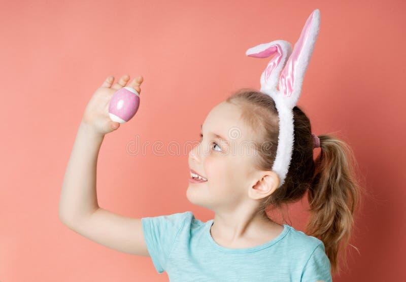 Lilla flickan i roliga kanin?ron rymmer ettf?rgat p?sk?gg, sidosikt royaltyfri bild