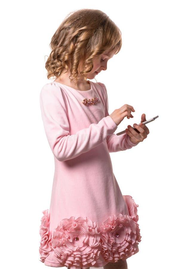 Lilla flickan i rosa färgklänning trycker på smartphoneskärmen på vit bakgrund isolerat royaltyfri bild