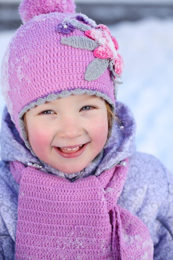Lilla flickan i rosa halsduk och hatt ler utomhus- fotografering för bildbyråer