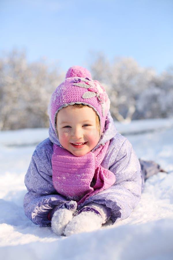 Lilla flickan i rosa halsduk och hatt ligger på magen på snö royaltyfri foto