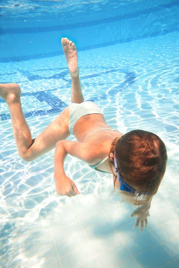 Lilla flickan i simning rullar med ögonen att simma som är undervattens- royaltyfri fotografi