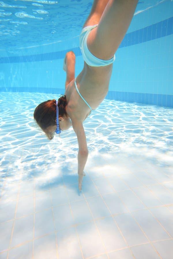 Lilla flickan i simning rullar med ögonen att simma som är undervattens- royaltyfria foton