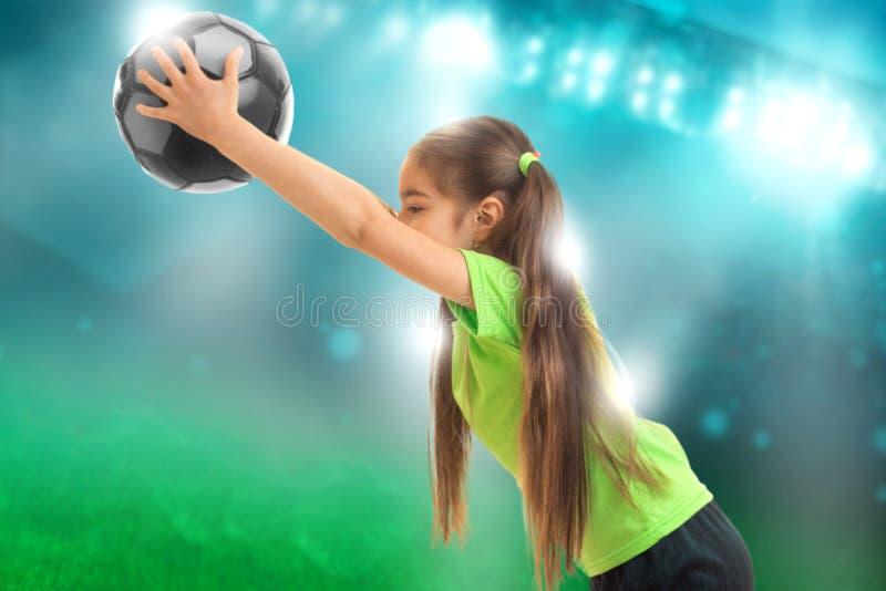 Lilla flickan i sportlikformig spelar fotboll royaltyfri bild