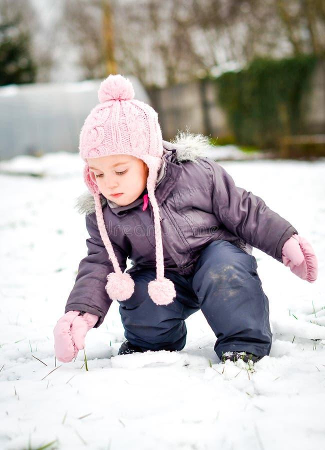 Lilla flickan i vinterkläder spelar i snö med hennes vinter arkivfoton