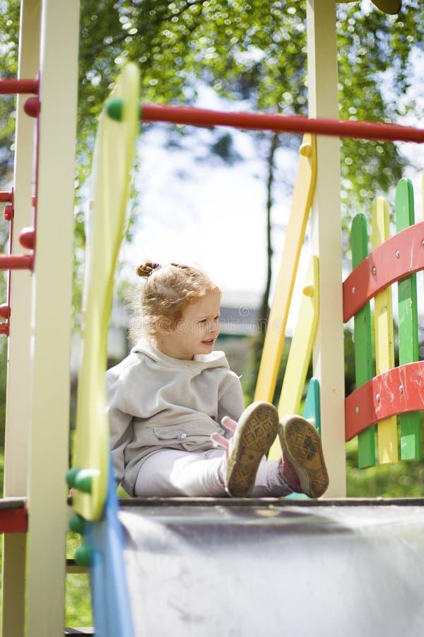Lilla flickan kl?ttrade p? barn glider p? en lekplats f?r barn och ?r j?tteglad att spela arkivbild