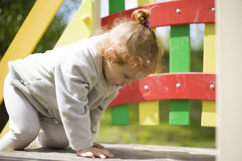 Lilla flickan kl?ttrade p? barn glider p? en lekplats f?r barn och ?r j?tteglad att spela arkivfoton