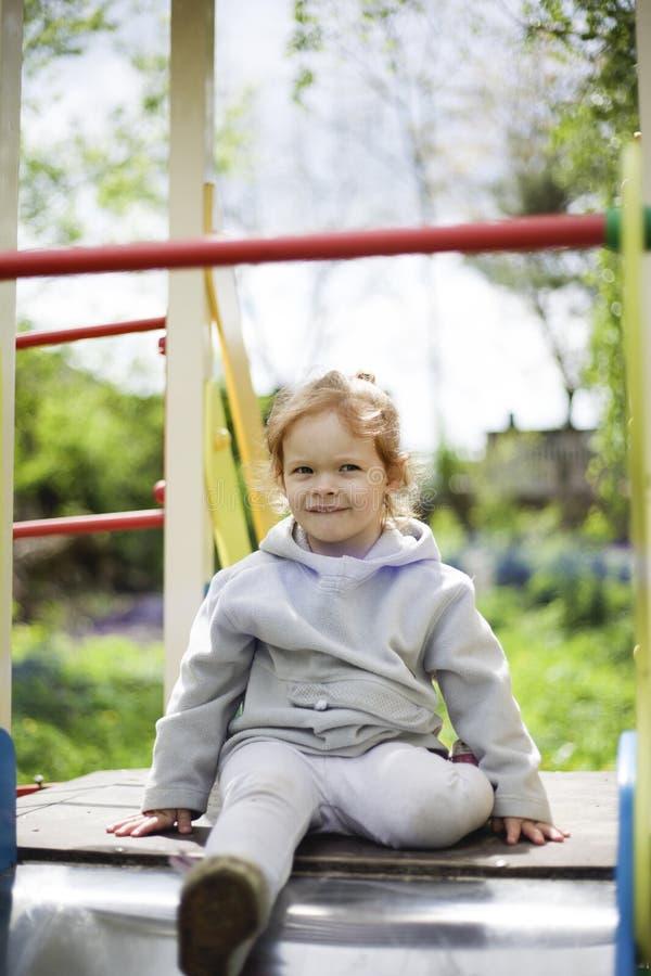 Lilla flickan kl?ttrade p? barn glider p? en lekplats f?r barn och ?r j?tteglad att spela fotografering för bildbyråer