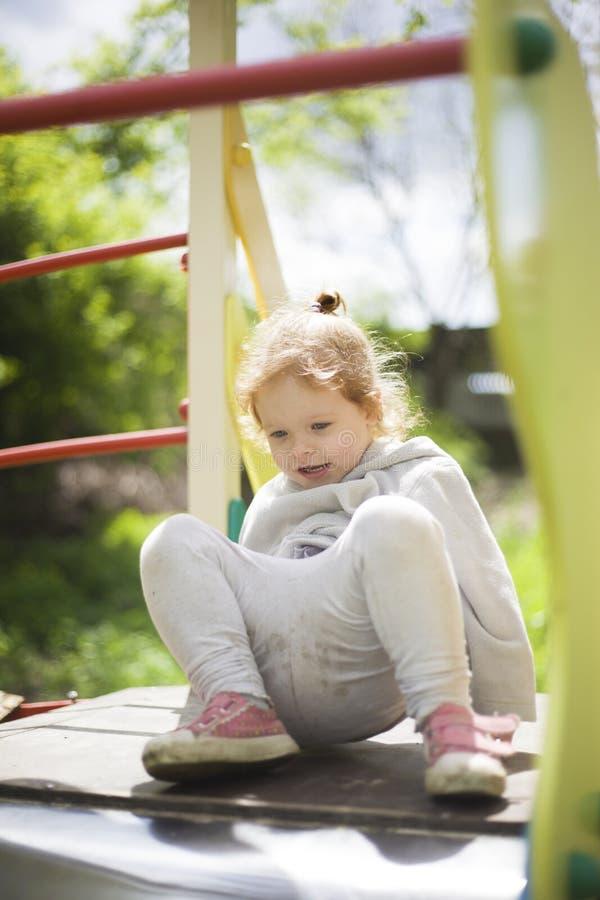 Lilla flickan kl?ttrade p? barn glider p? en lekplats f?r barn och ?r j?tteglad att spela royaltyfria foton