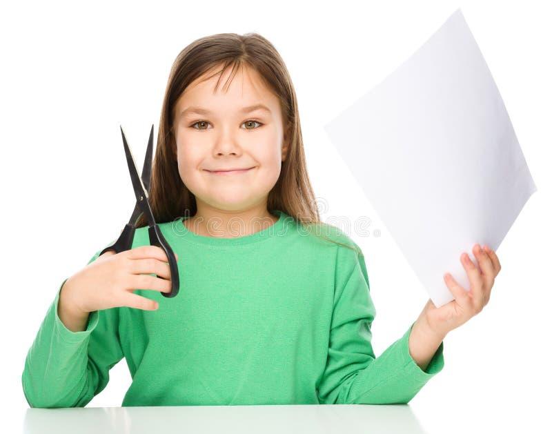 Lilla flickan klipper papper genom att använda sax arkivbild