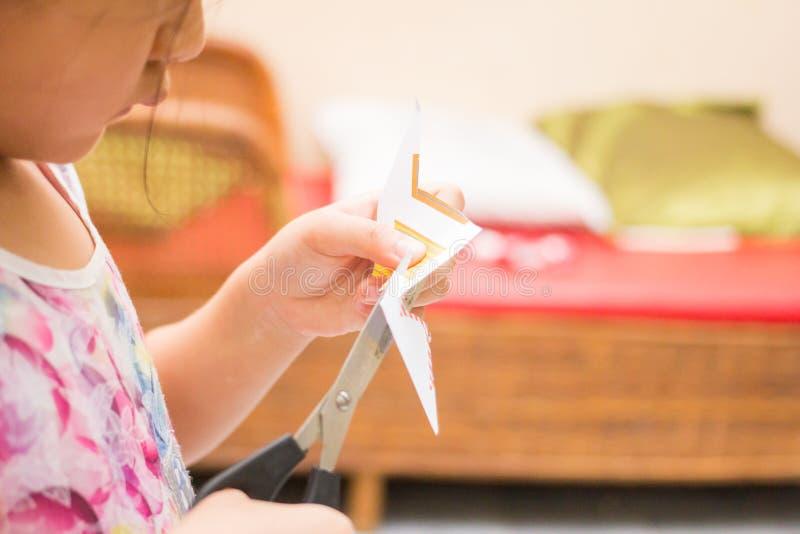 Lilla flickan klipper papperet royaltyfri bild
