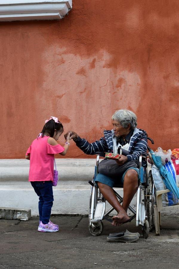Lilla flickan kysser handen av den etniska gamla kvinnan som sitter på rullstolen som rymmer julgåvaasken som tigger för allmosa  arkivfoto