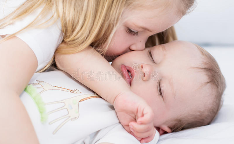 Lilla flickan kysser sova behandla som ett barn brodern royaltyfri fotografi