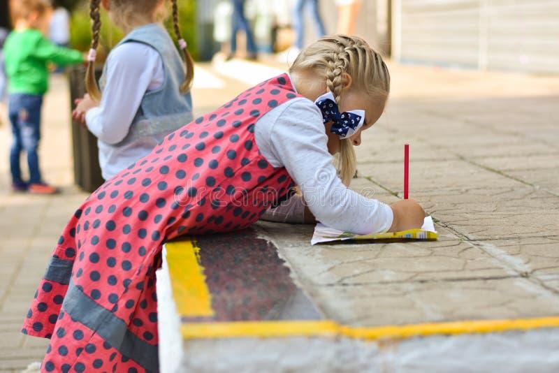 Lilla flickan lär att dra med en blyertspenna på ett stycke av papper från barntidskriften i skolgården royaltyfria bilder