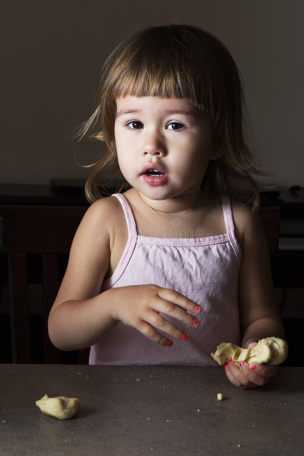Lilla flickan lär att göra deg royaltyfria bilder