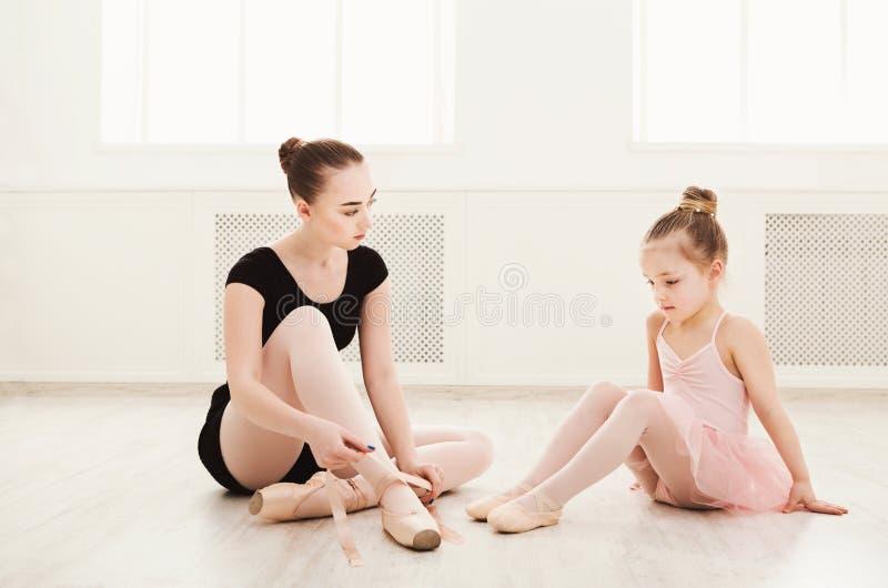 Lilla flickan lär balett med lärarekopieringsutrymme arkivbilder