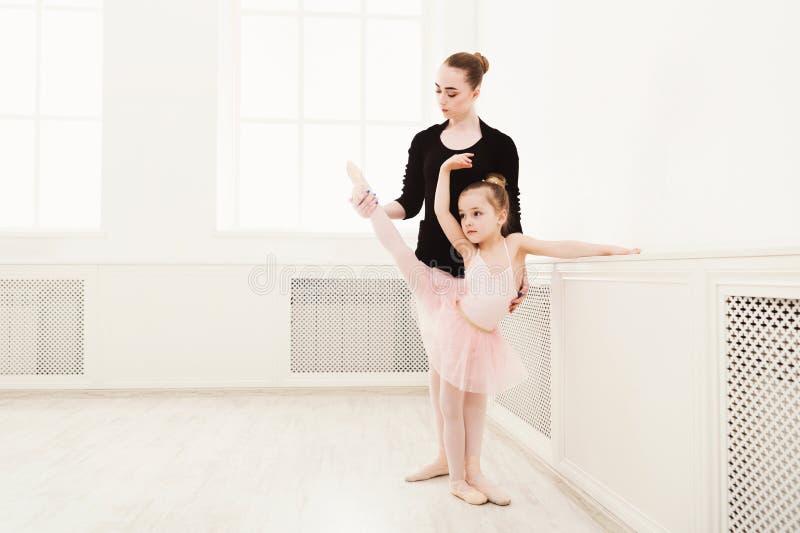 Lilla flickan lär balett med lärarekopieringsutrymme royaltyfria bilder