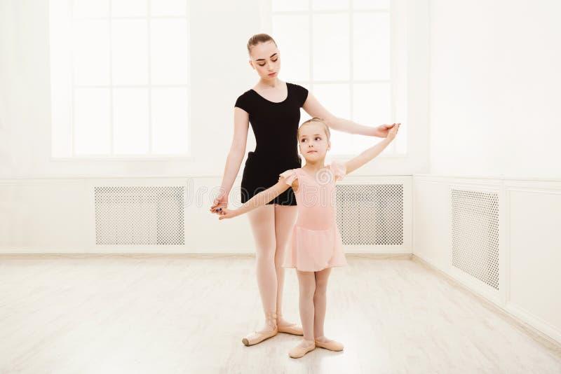 Lilla flickan lär balett med lärarekopieringsutrymme arkivfoton
