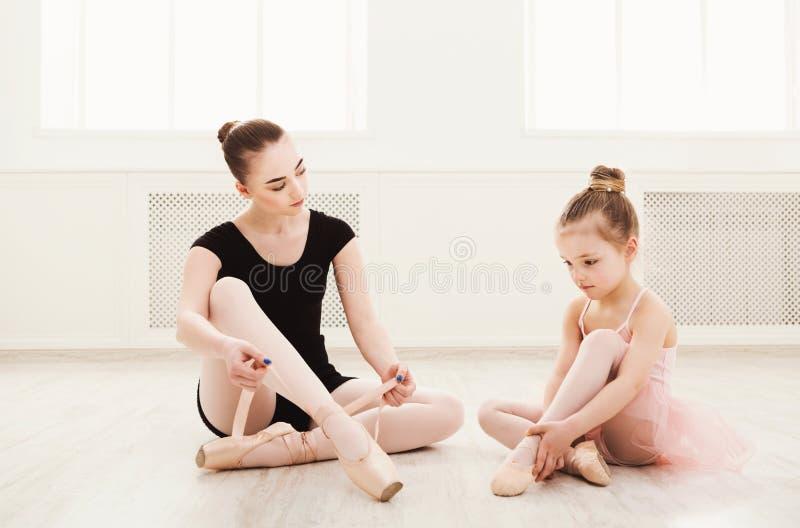 Lilla flickan lär balett med lärarekopieringsutrymme fotografering för bildbyråer