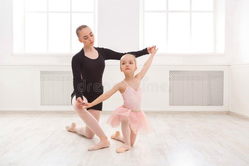 Lilla flickan lär balett med lärarekopieringsutrymme arkivbild