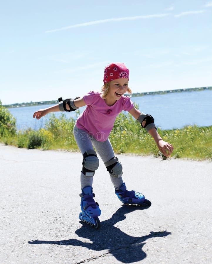 Lilla flickan lär till rullskridskon Flicka som lyckligt rullar på arkivbilder