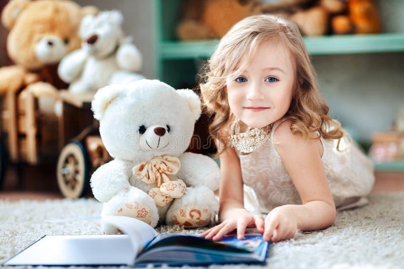Lilla flickan läser en bok i ett rum för barn` s med en leksaknallebjörn arkivbild