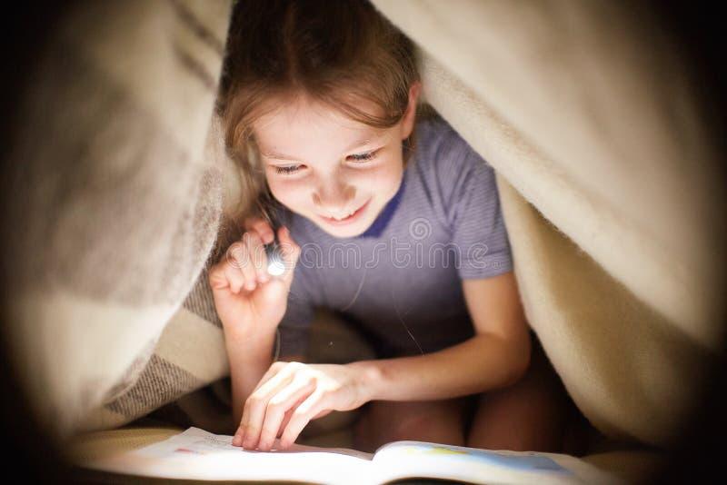 Lilla flickan läser en bok under en filt med en ficklampa i ett mörkt rum på natten arkivbilder