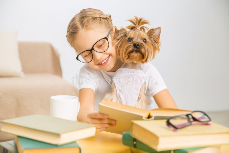 Lilla flickan läser med hennes hund fotografering för bildbyråer