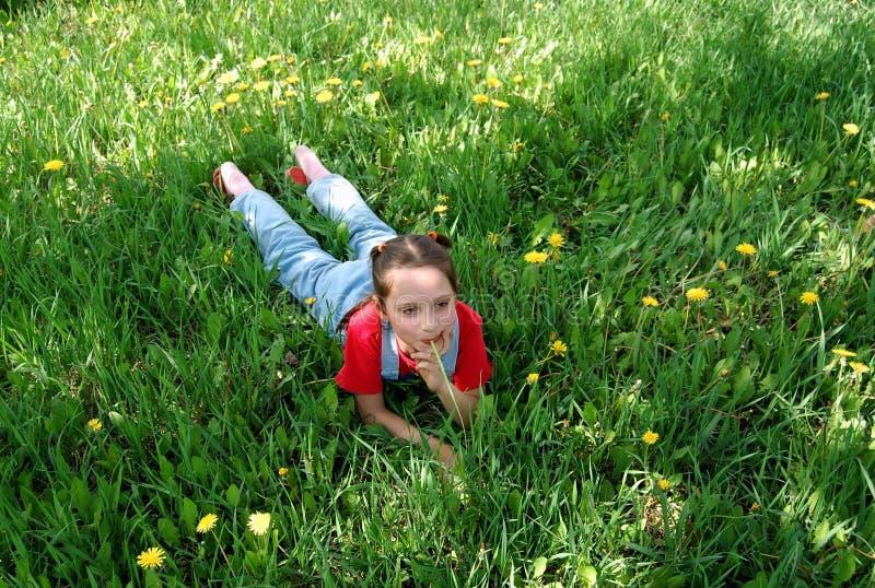 Lilla flickan ligger på en gräsmatta royaltyfri bild