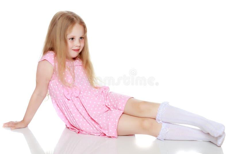 Lilla flickan ligger på golvet royaltyfria bilder