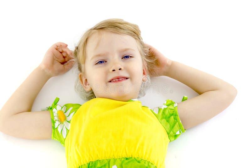Lilla flickan ligger på golvet arkivfoto