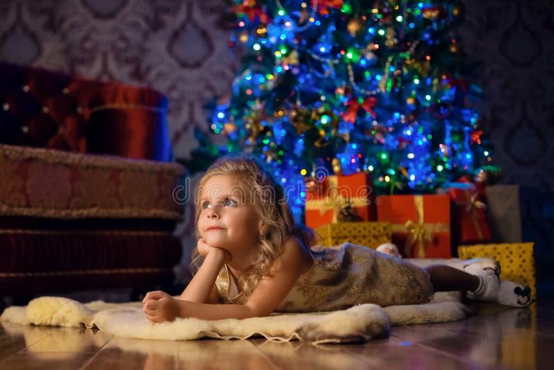 Lilla flickan ligger på golvet på trädet och drömmar av jul royaltyfri foto