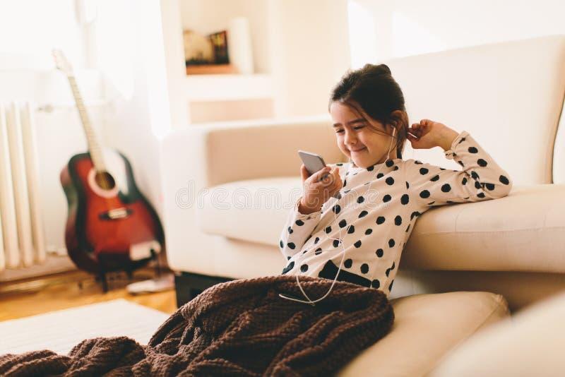 Lilla flickan lyssnar till musik royaltyfria bilder