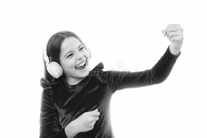 Lilla flickan lyssnar tr?dl?s h?rlurar f?r musik Online-musikkanal H?rlurar f?r musik f?r bruk f?r litet barn f?r flicka modern m arkivbilder