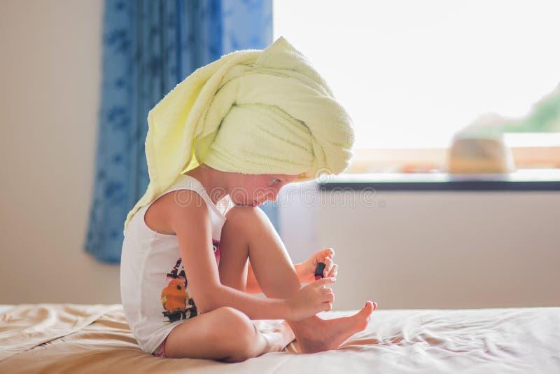 Lilla flickan målar hennes tånaglar hemma arkivfoto