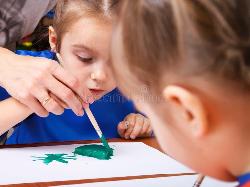Lilla flickan målar med en gouache arkivfoto