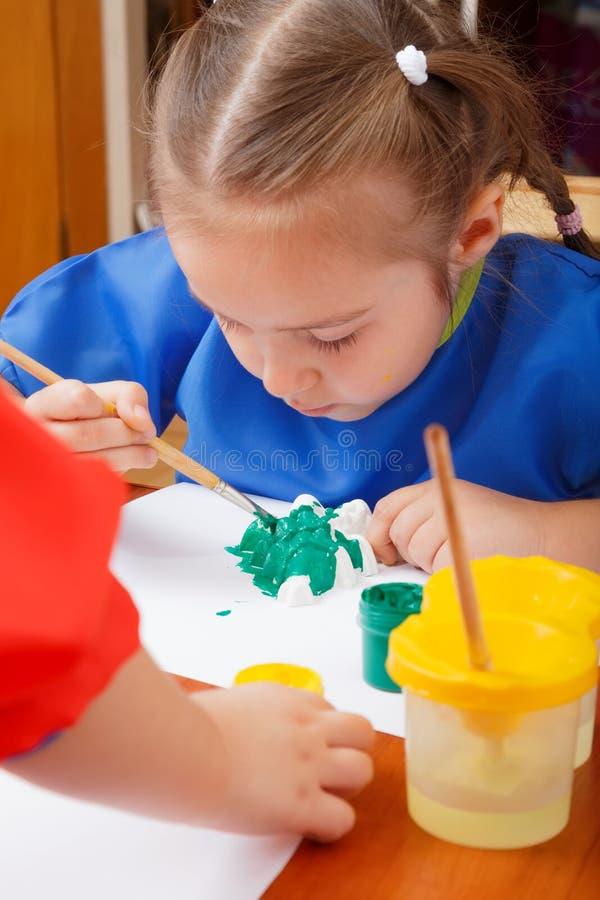Lilla flickan målar med gouache arkivfoton